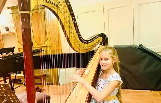 Geny se nezapřou: Poslechněte si, jak jedenáctiletá dcera producenta Čarodějky a operní pěvkyně hraje na harfu a zpívá